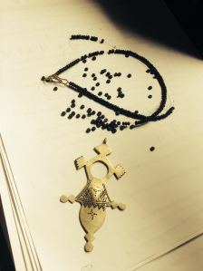 The Compass Necklace laying on the manuscript. It shall be mended...